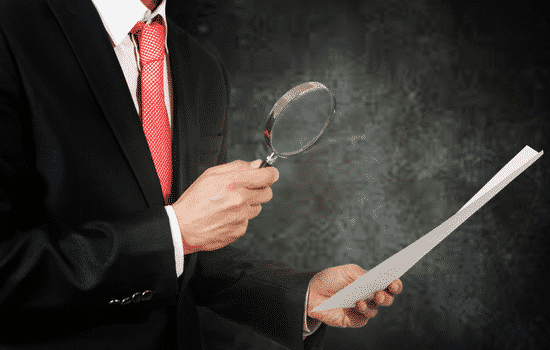 man in suit holding magnifying glass up to paper
