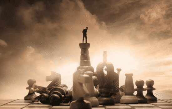 man standing on large chess pieces on chess board