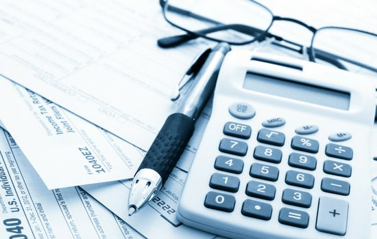 tax preparation services with calculator and glasses on table