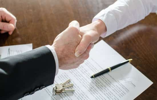 close up of handshake on wooden table with paperwork and pen