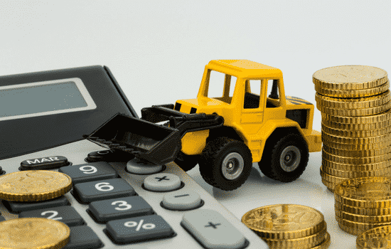 calcuator, toy dump truck, stack of coins, white background