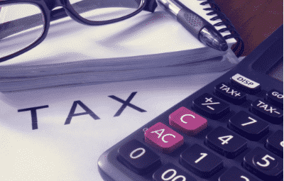 """State and local tax issues - the word """"tax"""" on paper, surrounded by calculator, glasses and pen"""
