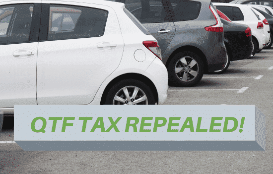 Cars in parking lot with text that reads OTF tax repealed.