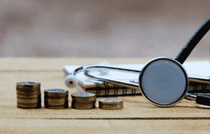 stethoscope with money and notebook on the table