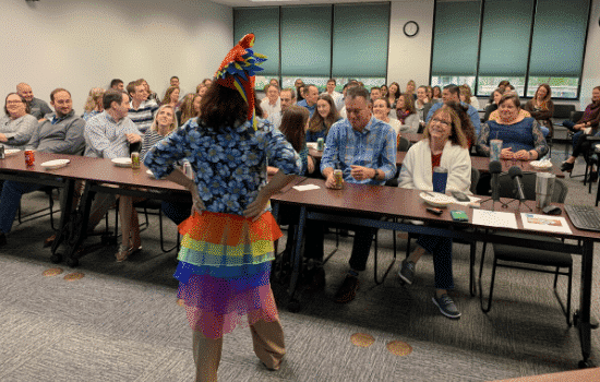 Suzanne Forbes in parrot hat and tailfeathers in front of JMCO Gainesville staff