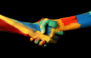 two painted multi-color hands shaking to show diversity