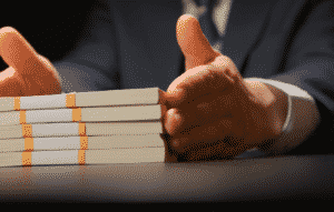 businessperson's hands surrounding a stack of money