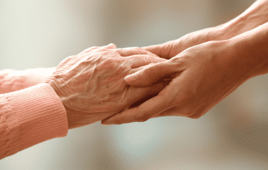 elderly woman's hands held caringly in younger woman's hands