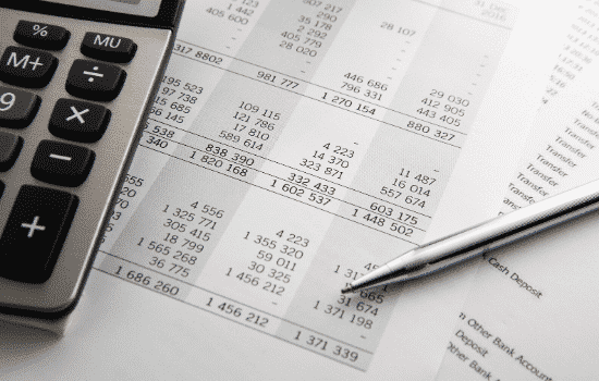 financial statements with pen and calculator on top