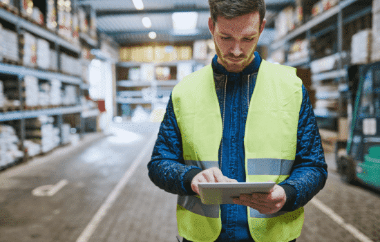 man in warehouse with tablet contemplating inventory write-down