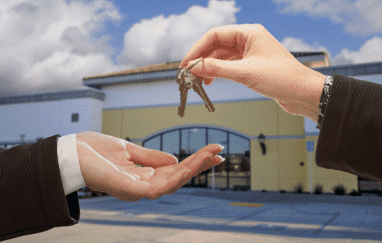 keys being handed to someone, commercial rental space in background