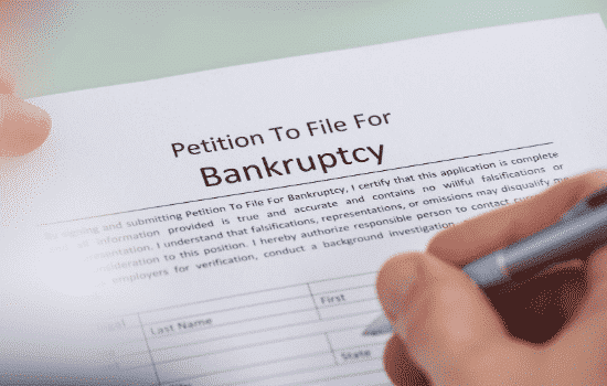 close up of person's hands filling out bankruptcy filing