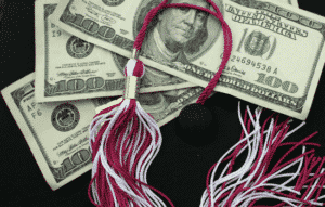 Dollar bills laying on top of a graduation cap with tassle.