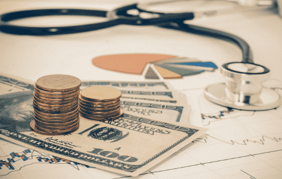 money and stethoscope on medical charts/graphs