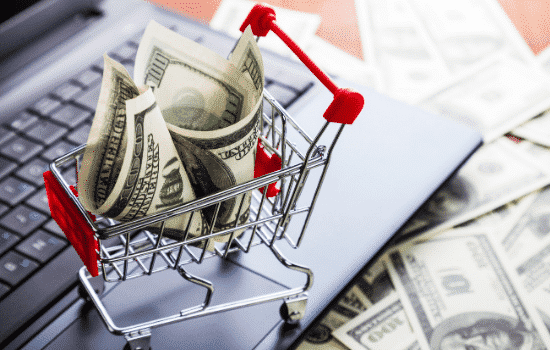 mini shopping cart on laptop with cash, represents online shopping through third-party marketplace facilitator