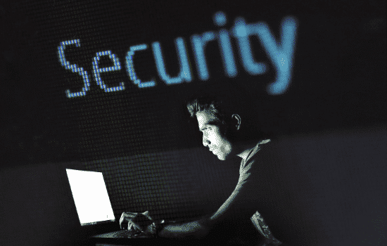 MAN SITS AT COMPUTER, WITH THE WORD SECURITY SITTING OVER TOP OF HIM