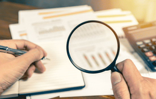 Magnifying glass over financial papers