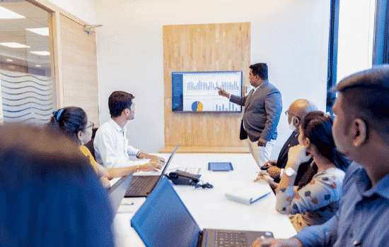 CFO leads meeting, points at TV screen