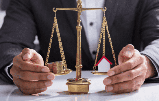 money and mini house on legal scale representing assets and protected
